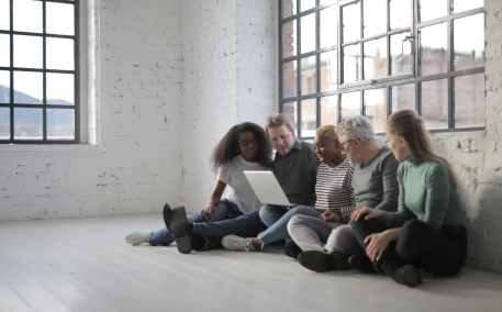 people sitting on floor while using laptop